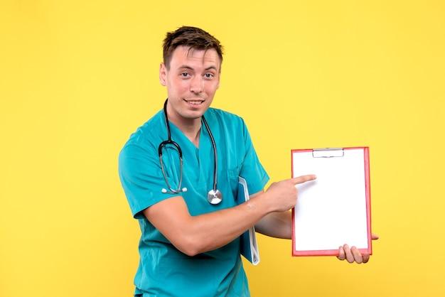 Vista frontal del joven médico sosteniendo análisis sobre pared amarilla