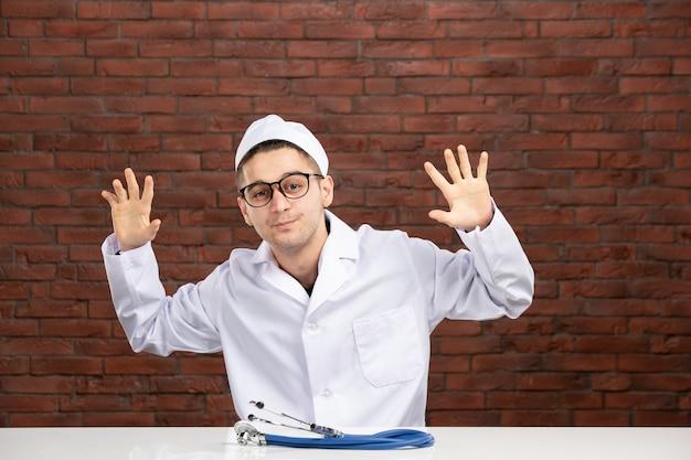 Vista frontal joven médico en traje médico blanco en la pared de ladrillos marrones