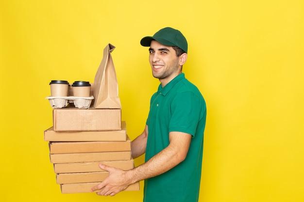 Vista frontal joven mensajero en camisa verde gorra verde sosteniendo cajas de entrega y tazas de café con sonrisa en amarillo