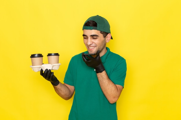 Vista frontal joven mensajero en camisa verde gorra verde sosteniendo tazas de café y hablando por teléfono con risa en amarillo