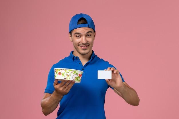 Vista frontal joven mensajero con capa uniforme azul con tarjeta blanca y recipiente de entrega redondo en pared rosa claro