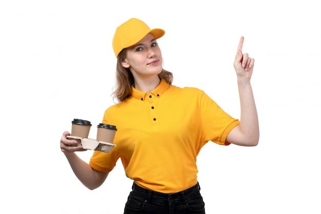 Una vista frontal joven mensajero femenino trabajadora del servicio de entrega de alimentos con tazas de café sonriendo en blanco
