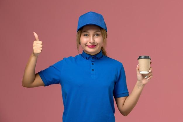 Vista frontal joven mensajero sonriente en uniforme azul posando sosteniendo una taza de café de entrega marrón, mujer de entrega uniforme de trabajo de servicio