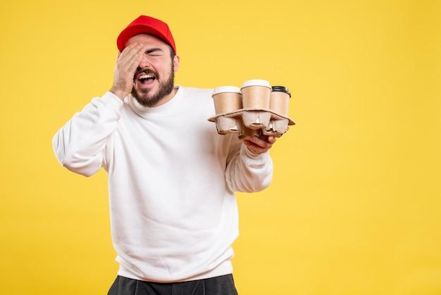 Vista frontal joven mensajero sosteniendo café de entrega