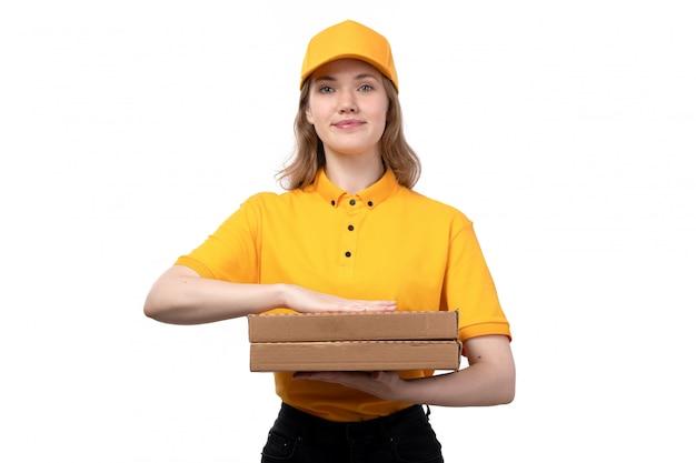 Una vista frontal joven mensajero trabajadora del servicio de entrega de alimentos con cajas de pizza sonriendo en blanco