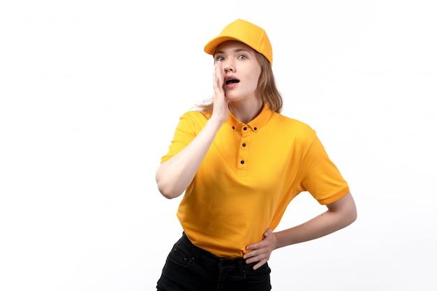 Una vista frontal joven mensajero trabajadora del servicio de entrega de alimentos posando y susurrando en blanco