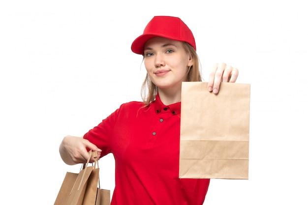 Una vista frontal joven mensajero trabajadora del servicio de entrega de alimentos sonriendo sosteniendo la caja con comida en blanco