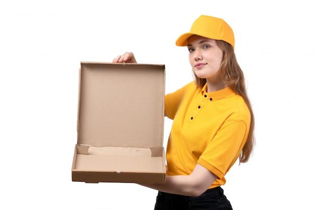 Una vista frontal joven mensajero trabajadora del servicio de entrega de alimentos sonriendo sosteniendo una caja de pizza vacía en blanco