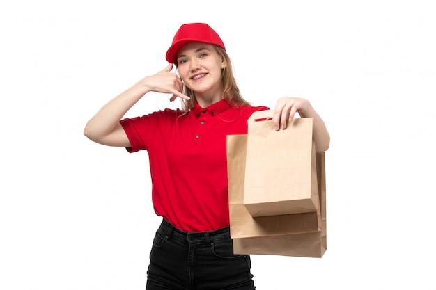 Una vista frontal joven mensajero trabajadora del servicio de entrega de alimentos sonriendo sosteniendo paquetes de entrega en blanco
