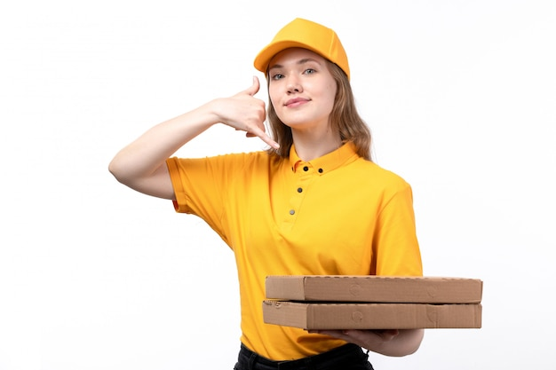 Una vista frontal joven mensajero trabajadora del servicio de entrega de alimentos sosteniendo cajas de pizza y mostrando señal de conversación telefónica en blanco