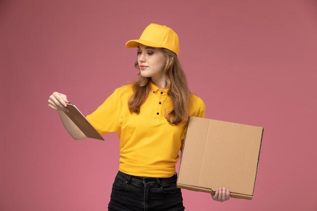 Vista frontal joven mensajero en uniforme amarillo con caja de comida de entrega y bloc de notas en el trabajo de escritorio rosa trabajador de servicio de entrega uniforme