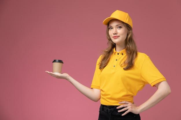 Vista frontal joven mensajero en uniforme amarillo capa amarilla sosteniendo café con una sonrisa en el fondo rosa oscuro servicio de entrega uniforme trabajadora