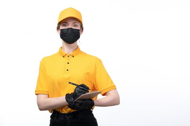 Una vista frontal joven mensajero en uniforme amarillo guantes negros y máscara negra sosteniendo el bloc de notas escribiendo órdenes