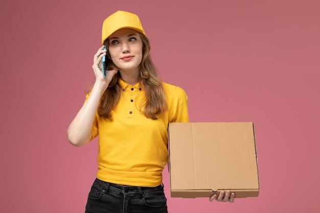 Vista frontal joven mensajero en uniforme amarillo hablando por teléfono sosteniendo el paquete con comida sobre fondo rosa trabajo de escritorio uniforme trabajador de servicio de entrega