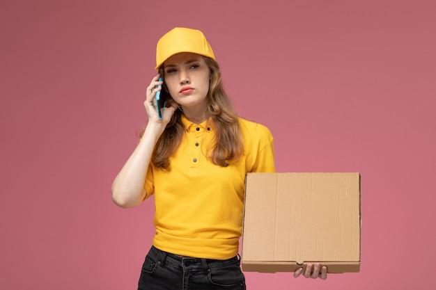 Vista frontal joven mensajero en uniforme amarillo sosteniendo caja de comida y hablando por teléfono sobre el fondo rosa oscuro trabajador de servicio de trabajo de entrega uniforme