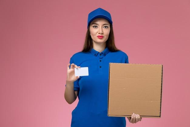 Vista frontal joven mensajero en uniforme azul y capa con caja de comida y tarjeta de plástico en la pared rosa