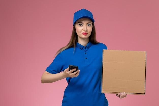 Vista frontal joven mensajero en uniforme azul y capa con caja de comida vacía y teléfono en la pared rosa
