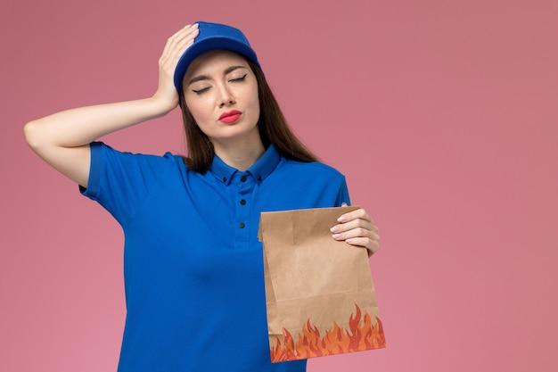 Vista frontal joven mensajero en uniforme azul y capa con paquete de comida de papel que tiene dolor de cabeza en la pared rosa