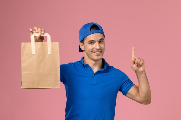 Vista frontal joven mensajero en uniforme azul y capa con paquete de papel de entrega en sus manos en la pared rosa