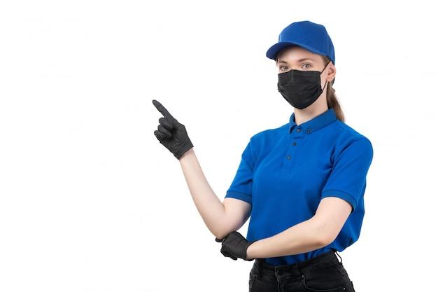 Una vista frontal joven mensajero en uniforme azul guantes negros y máscara negra señalando con el dedo