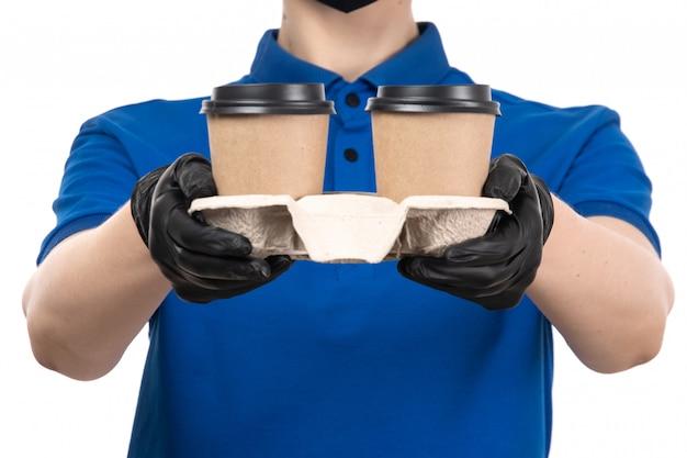 Una vista frontal joven mensajero en uniforme azul máscara negra y guantes sosteniendo tazas de café