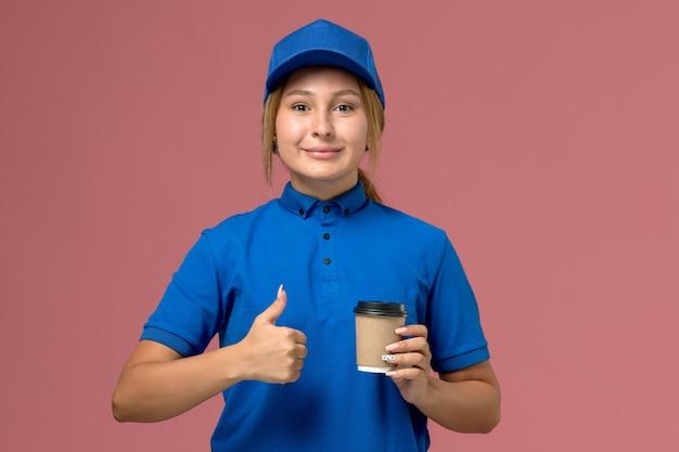 Vista frontal joven mensajero en uniforme azul posando y sosteniendo la taza de café de entrega en la pared rosa, servicio de entrega uniforme mujer
