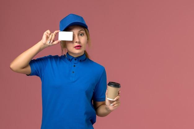 Vista frontal joven mensajero en uniforme azul posando sosteniendo una taza de café y tarjeta blanca, trabajador de trabajo de mujer de entrega uniforme de servicio