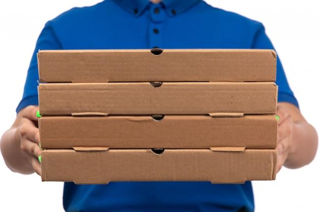 Una vista frontal joven mensajero en uniforme azul sosteniendo paquetes de entrega de alimentos con una sonrisa