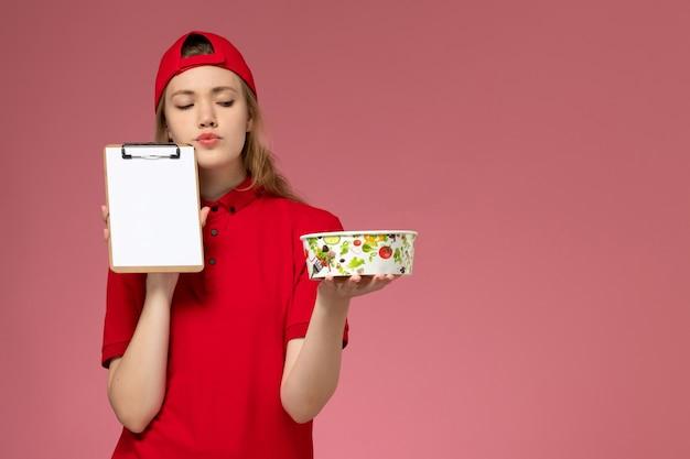 Vista frontal joven mensajero en uniforme rojo y capa sosteniendo el cuenco de entrega y el bloc de notas pensando en la pared rosa
