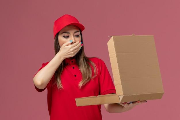 Vista frontal joven mensajero en uniforme rojo sosteniendo la caja de comida de entrega y abriéndola sobre fondo rosa claro servicio de entrega de trabajo uniforme empresa