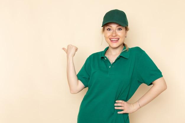 Vista frontal joven mensajero en uniforme verde y capa verde sonriendo y posando en el uniforme de mujer espacio crema