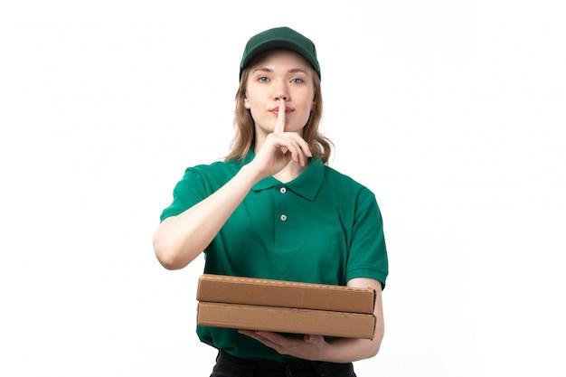 Una vista frontal joven mensajero en uniforme verde sonriendo sosteniendo cajas de comida mostrando signo de silencio