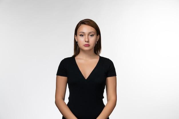 Vista frontal joven mujer atractiva en camisa negra de pie sobre la superficie blanca