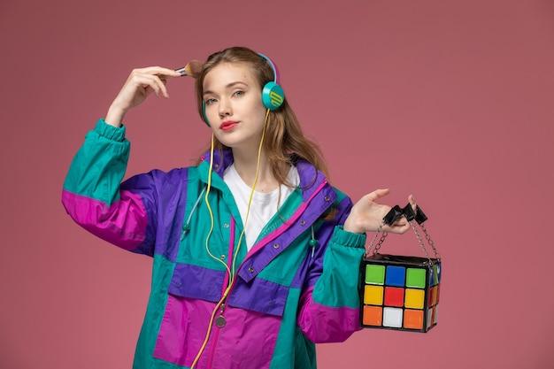 Vista frontal joven mujer atractiva en camiseta blanca abrigo de color posando escuchando música en la pared rosa modelo pose femenina fotografía en color