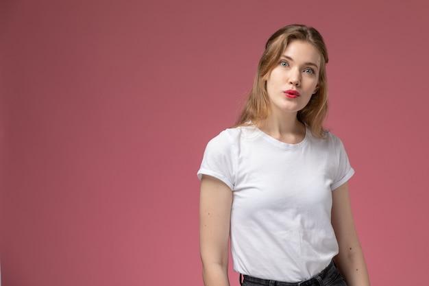 Vista frontal joven mujer atractiva en camiseta blanca posando con expresión de sorpresa en la pared rosa modelo pose femenina color hembra joven