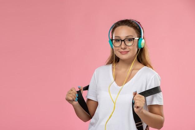 Vista frontal joven mujer atractiva en camiseta blanca posando y smi escuchando música sobre fondo rosa