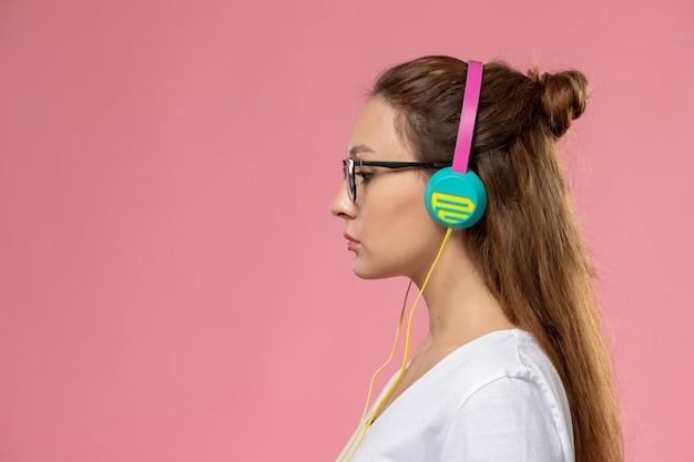Vista frontal joven mujer atractiva en camiseta blanca simplemente posando y escuchando música a través de auriculares en el fondo rosa