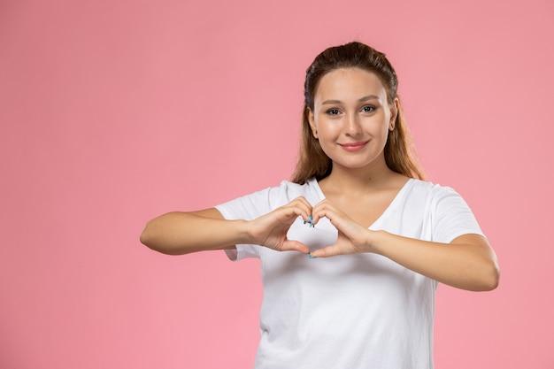 Vista frontal joven mujer atractiva en camiseta blanca con sonrisa mostrando signo de corazón sobre fondo rosa