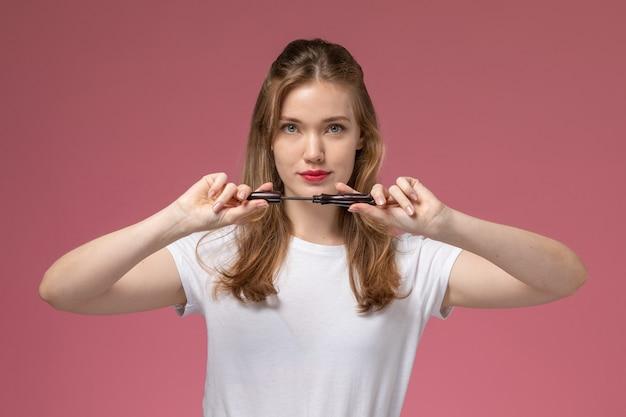 Vista frontal joven mujer atractiva en camiseta blanca sosteniendo rímel en la pared de color rosa oscuro modelo color mujer joven