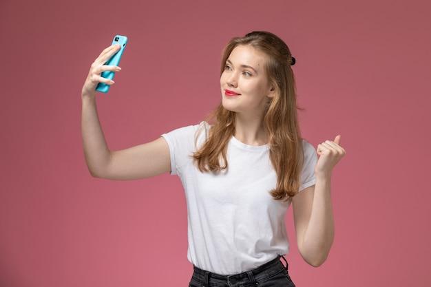 Vista frontal joven mujer atractiva en camiseta blanca tomando un selfie con sonrisa en la pared rosa modelo color mujer joven