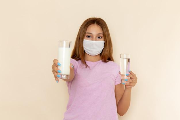 Vista frontal joven mujer atractiva en camiseta rosa y jeans sosteniendo vasos de agua y leche con máscara