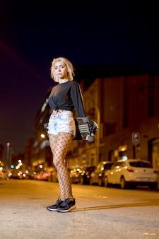 Vista frontal de una joven mujer bonita mirando la cámara en pantalones cortos mientras está de pie en la calle sosteniendo una patineta en la noche en la ciudad