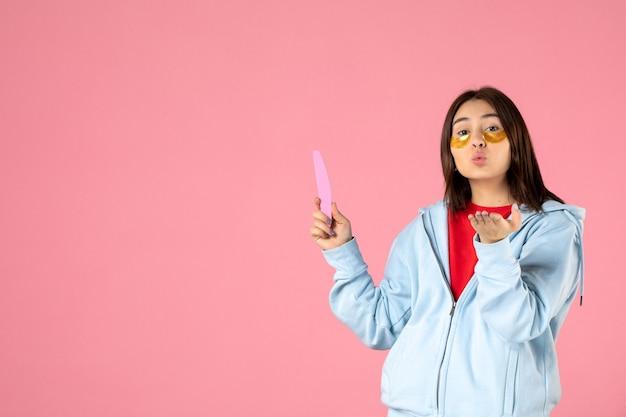 Vista frontal joven mujer bonita con parches en los ojos y lima de uñas sobre fondo rosa