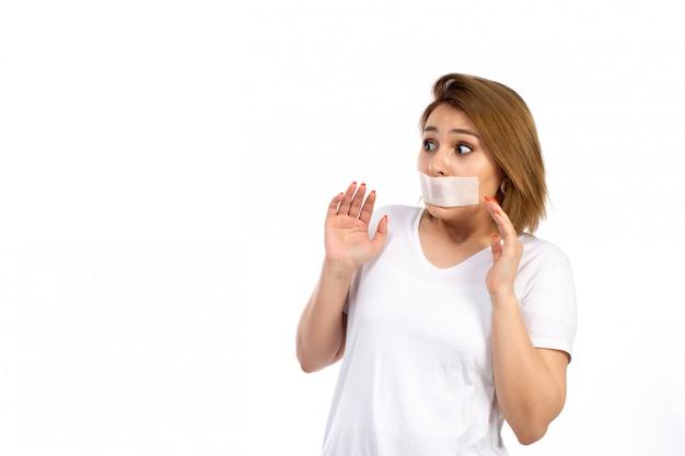 Una vista frontal joven mujer en camiseta blanca con una venda blanca alrededor de la boca por miedo a las amenazas en el blanco