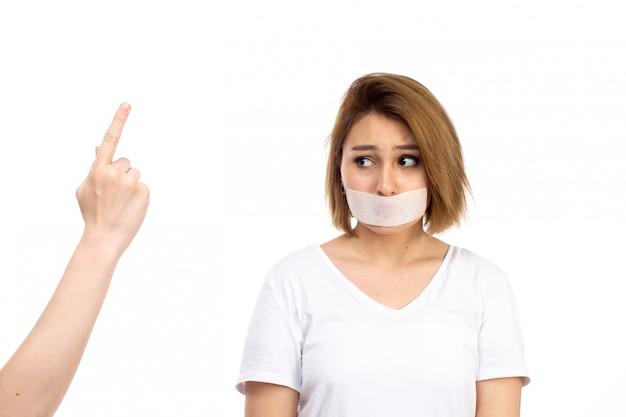 Una vista frontal joven mujer en camiseta blanca con vendaje blanco alrededor de su boca se declara culpable perdón expresión en el blanco