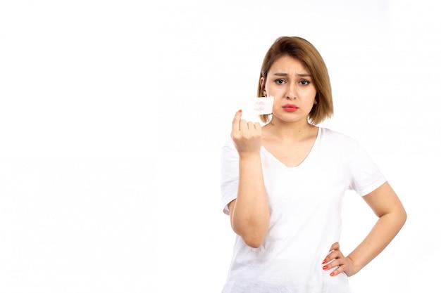 Una vista frontal joven mujer en camiseta blanca con vendaje blanco alrededor de su boca despegando en el blanco