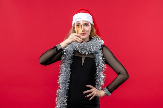 Vista frontal joven mujer celebrando el año nuevo en la pared roja emoción vacaciones de navidad