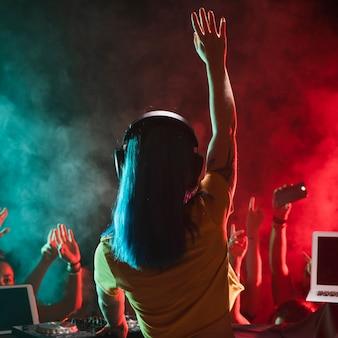 Vista frontal joven mujer dj entretenida multitud