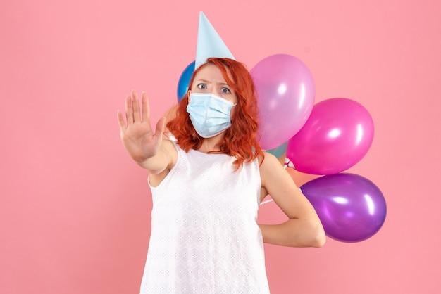 Vista frontal joven mujer escondiendo globos de colores en máscara estéril sobre fondo rosa fiesta covid- año nuevo navidad