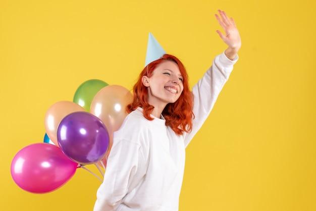 Vista frontal joven mujer escondiendo lindos globos de colores en el escritorio amarillo año nuevo color emoción regalo niño mujer